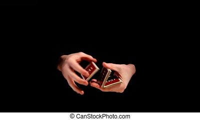 Magician making his trick with cards on black background -...