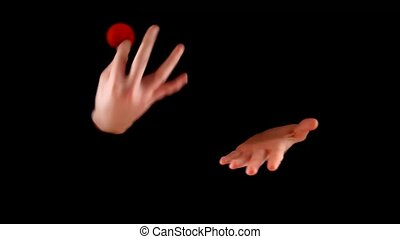 Magician performing with two red balls on black background -...