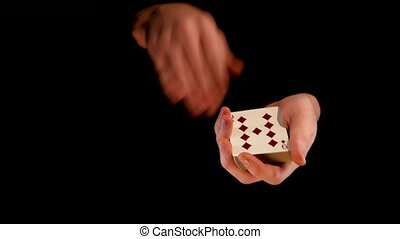 Magician shows his trick with cards on black background -...
