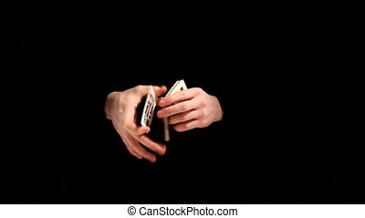 Magic playing card trick kardistri on black background -...