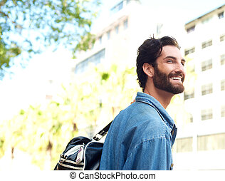 Happy smiling young man standing outdoors with travel bag -...