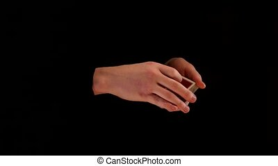 Magician shows a trick with cards on black background -...