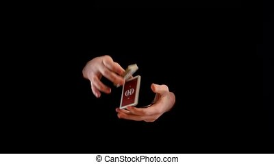 Unusual trick with playing cards on black background -...
