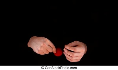 Magician making trick with red balls on black background -...