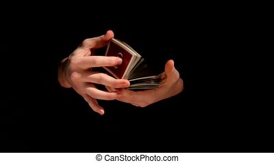 Magician`s hands making trick with playing cards on black...