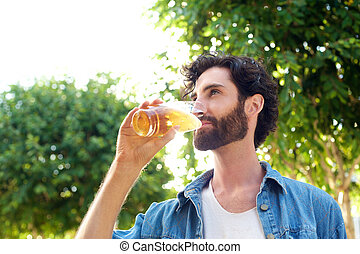 Handsome young man drinking beer outdoors - Portrait of a...