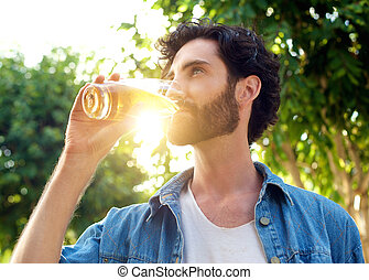 Handsome young man drinking beer in summer - Close up...