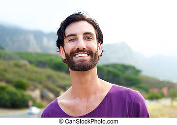 Happy young man with beard smiling outdoors
