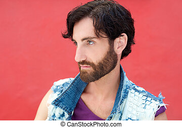Male fashion model with beard posing on red background