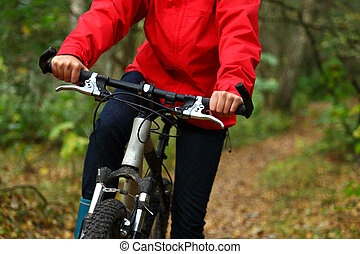 Bike - Biking. Woman on mountainbike in autumn forest.