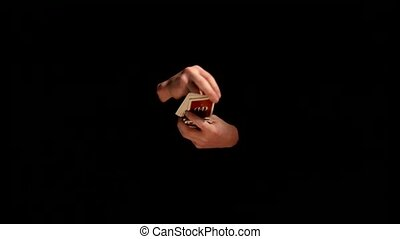 Wizard showing trick with playing card on black background -...