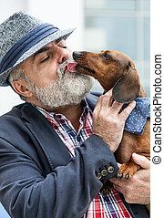 Attractive old man with beard and hat with dog teckel -...