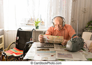 Old Man Reading Newspaper While Listening at Radio - Happy...