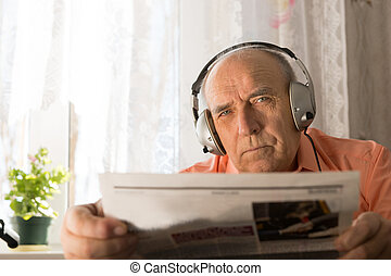 Serious Old Age Man with Headset Holding Newspaper - Close...