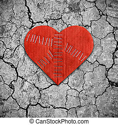 Broken heart on dry cracked soil