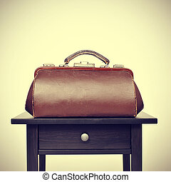 old doctors bag on a table, with a retro filter effect - an...