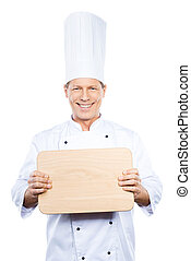 Copy space on his cutting board. Confident mature chef in...