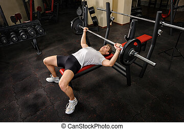 young man doing bench press workout in gym - handsome young...