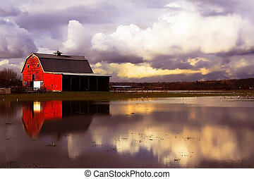 Red barn surrounded by flood water.