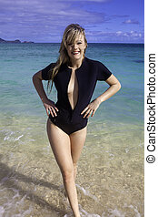 girl in wetsuit at the beach - beautiful blond girl in...