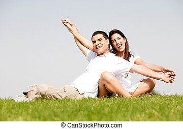 Young Couple Sitting Together Outside - Cute young couple in...