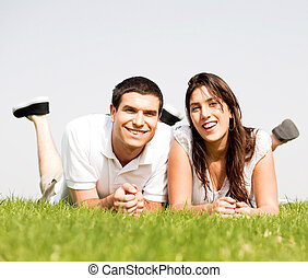 happy Couple lie down on grass - love Couple lie down on...
