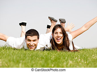 cute young Couple lie down on grass in a hands outstretched