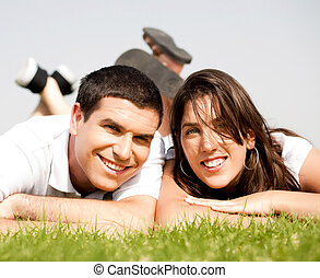 happy young Couple lie down on grass and smile