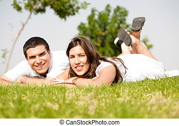beautiful young Couple lie down on grass and smile