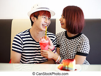 young asian couple enjoy feeding cake and drink
