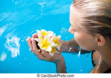 Beautiful young woman in spa holding exotic flowers