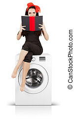 Girl Reading on a Washing Machine - Young housewife doing...