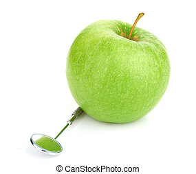 Green apple and dental tools isolated