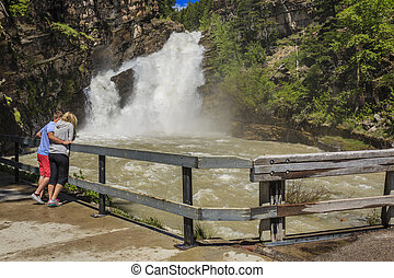 Roaring Waterfalls - A couple enjoy the fast flowing...