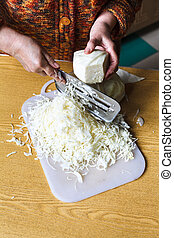 woman shredding cabbage by manual slaw cutter on table