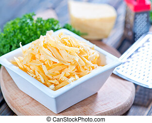 grated cheese in bowl and on a table