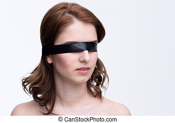 Blindfold beautiful woman over gray background