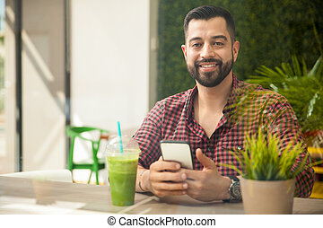 Texting in a smoothie shop - Attractive young man doing some...