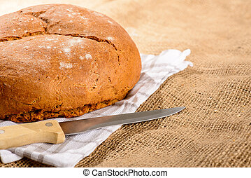 Image of bread loaf and knife - Fresh and warm. Cropped...