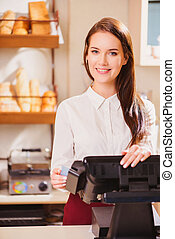Beautiful young saleswoman in a bakery - Welcome to our...