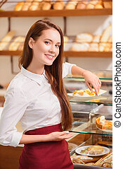 Beautiful young saleswoman in a bakery - Proud of what we...