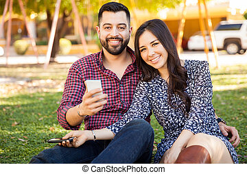Hispanic couple using smartphones - Portrait of a good...
