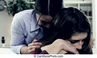 Woman crying hugging daughter - Sad woman crying with...