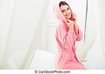 Beautiful young woman getting ready to take a bath