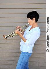 Female trumpet player. - Mature female trumpet player...