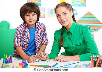 Little boy and teacher drawing in a preschool center -...