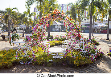 tricycle was decorated with flowers. - The chair was...
