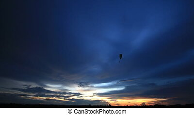 Paragliding on sunrise or sunset  background.