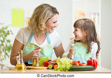 mother and her kid preparing healthy food and having fun -...