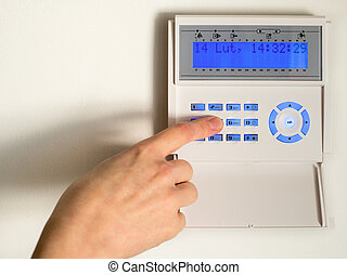 pressing the code on a house alarm - Arming a home or...